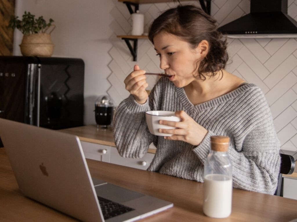 woman sitting in front of work computer eating