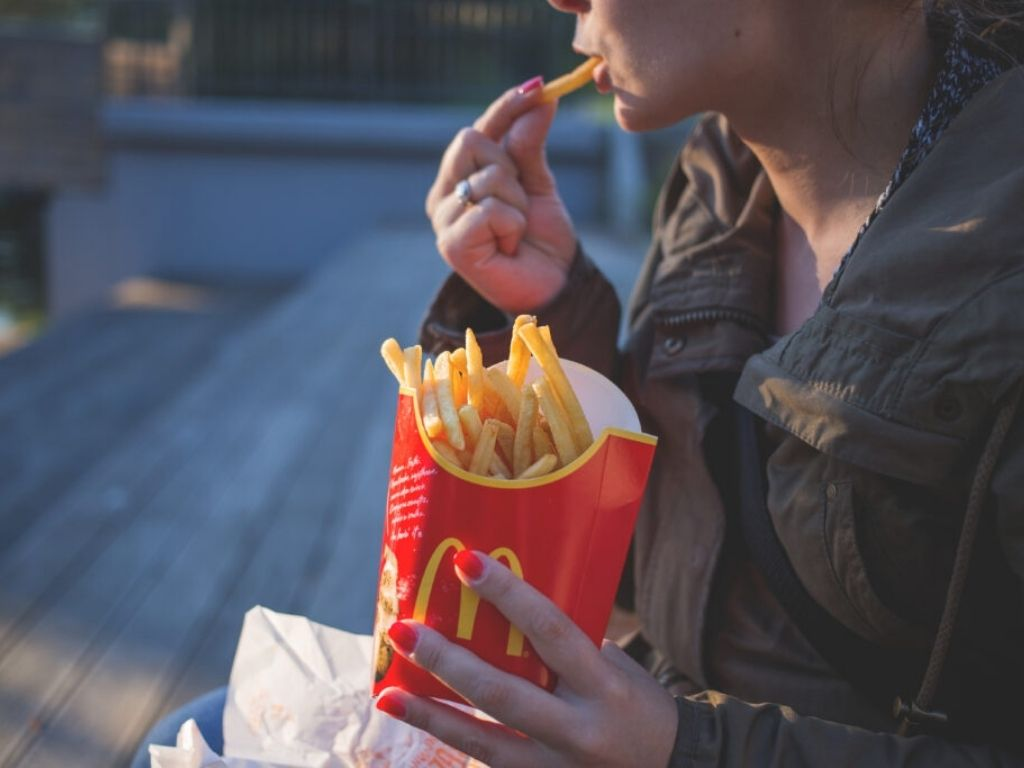 Woman eating McDonalds French Fies