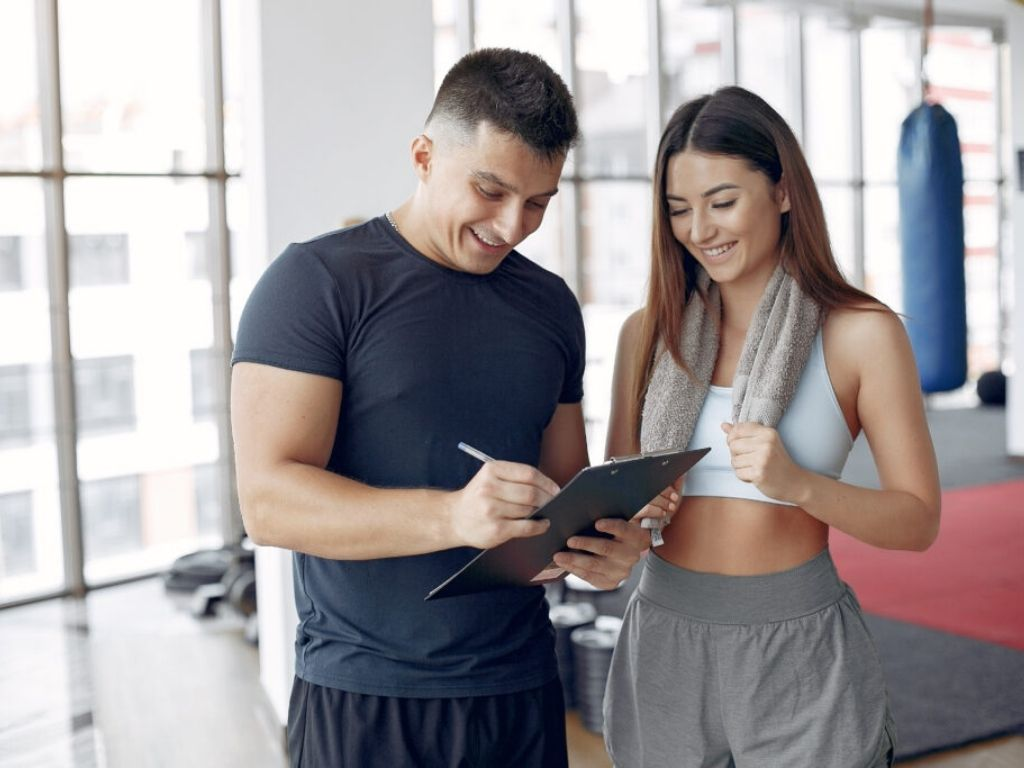 Woman in sportswear talking to her personal fitness trainer