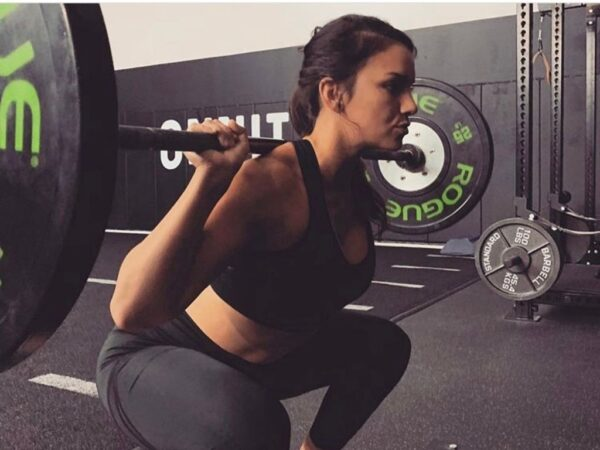 Woman doing heavy squats with barbell