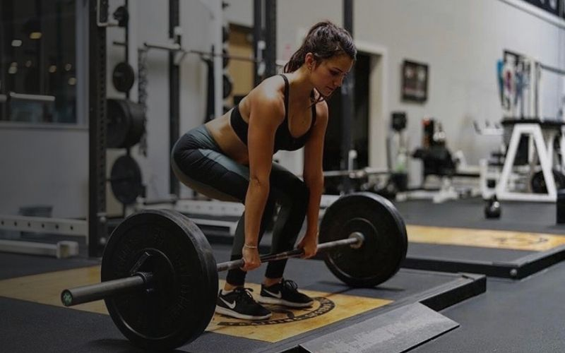 Woman at gym using a barbell