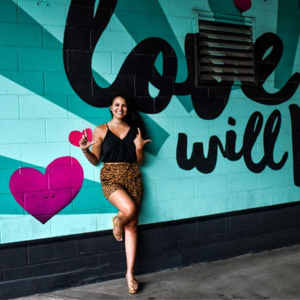 Girl in leopard print shorts leaning against graffiti wall that says