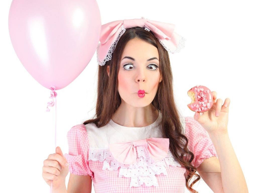 Girl making fish face wearing pink dress, pink bow, and holding pink donut