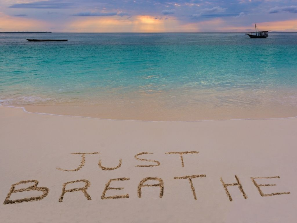 """""""Just Breath"""" written in the sand on the beach"""