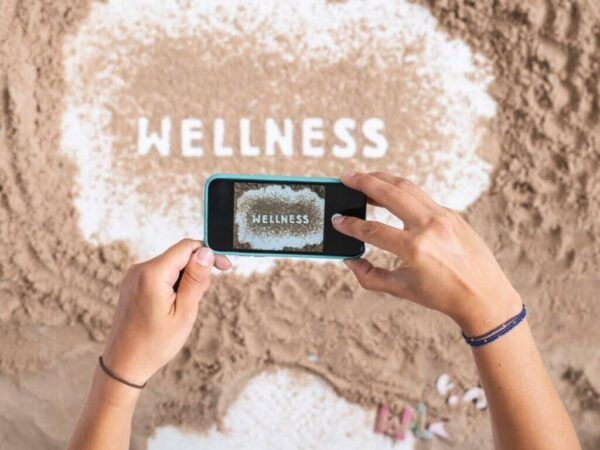 "girl taking selfie of the word ""wellness"" written in the sand"