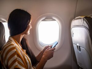 Young smiling Latin Woman using mobile phone on airplane