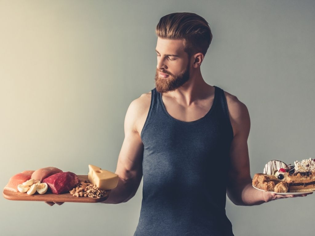 young bearded sportsman holding a wooden tray with healthy food and a plate with sweets