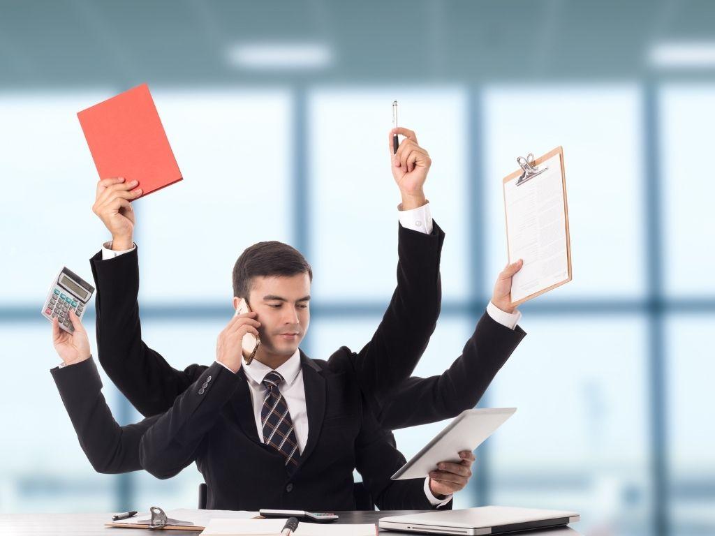 Multitasking Busy Man sitting at desk