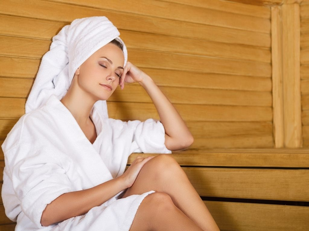 Woman relaxing in white robe in an infrared sauna