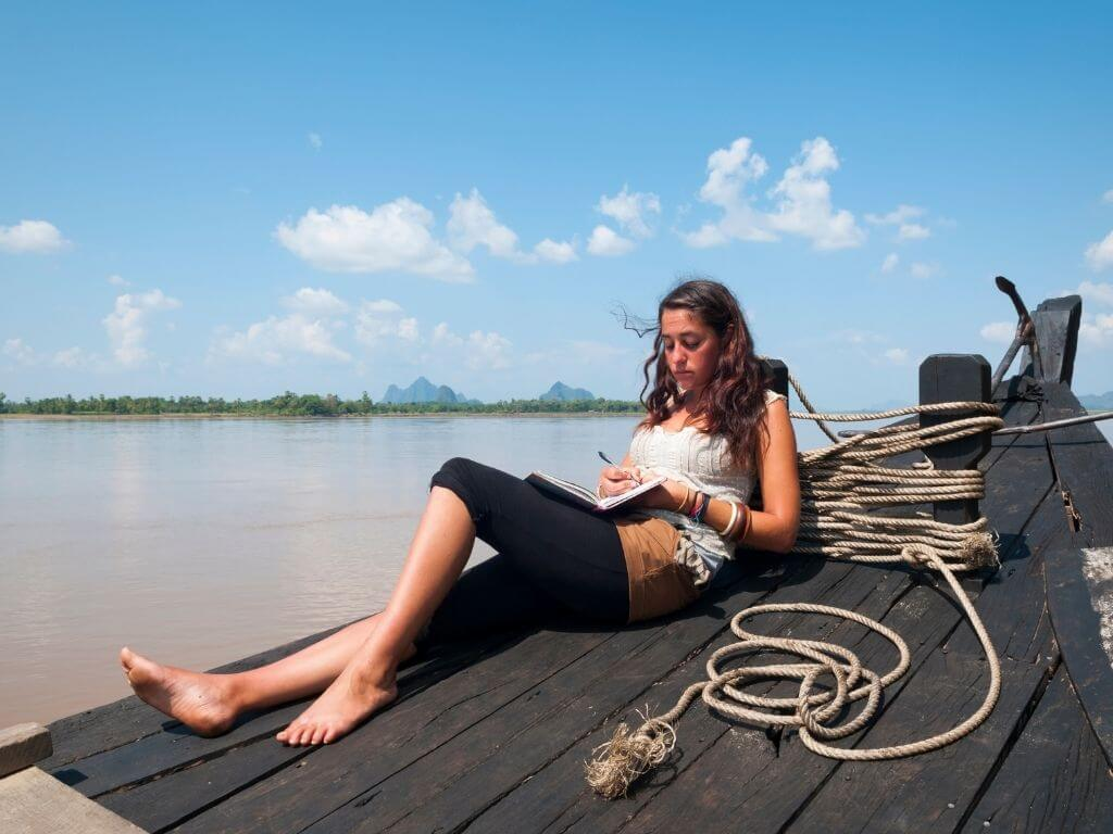 Woman laying on dock by water writing in journal