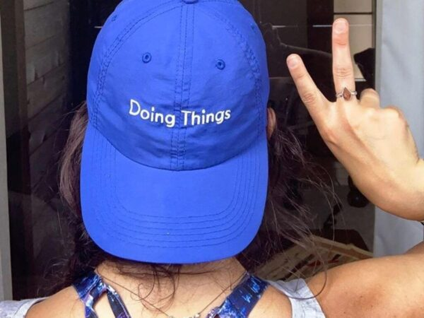 """Back view of girl wearing blue hat backwards that says """"Doing Things"""" while holding up the peace sign"""