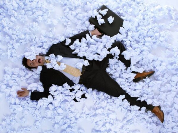Man in Business Suit laying on ground stressed and overwhelmed