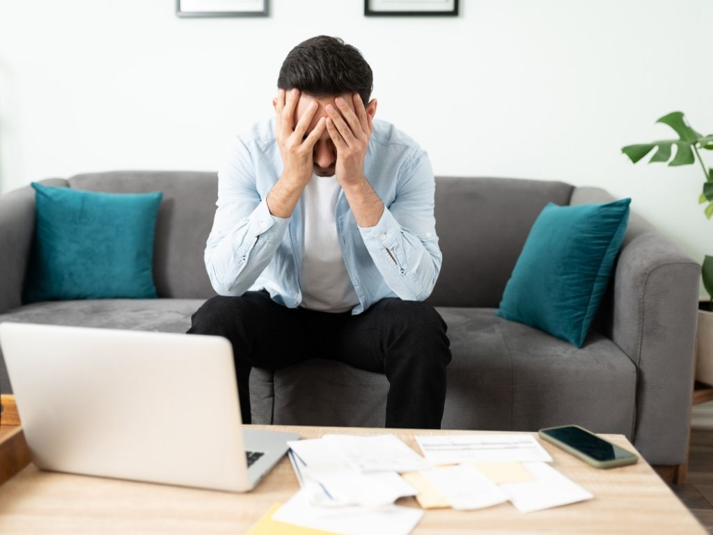 Man sitting on couch with hands over face looking stressed