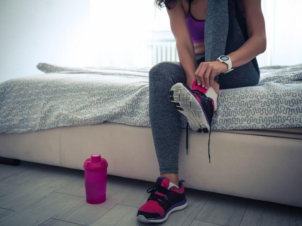 Woman sitting on bed putting on running shoes