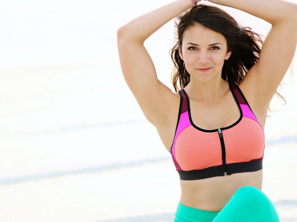 Brunette model in sportswear posing on the beach