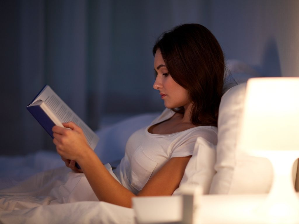 Young woman reading book in bed at night
