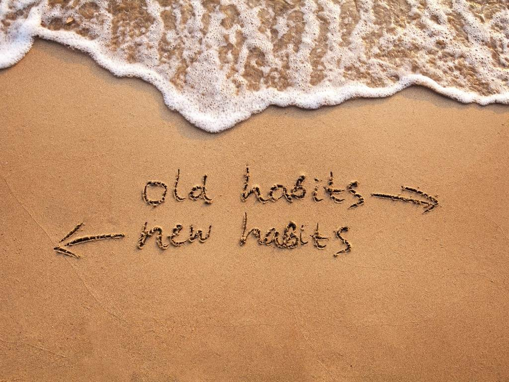 old habits vs new habits concept written in sand on beach