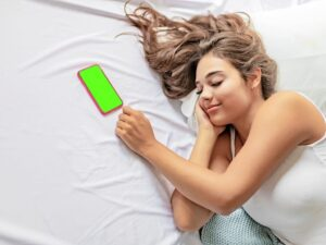 Beautiful woman laying in bed with iphone