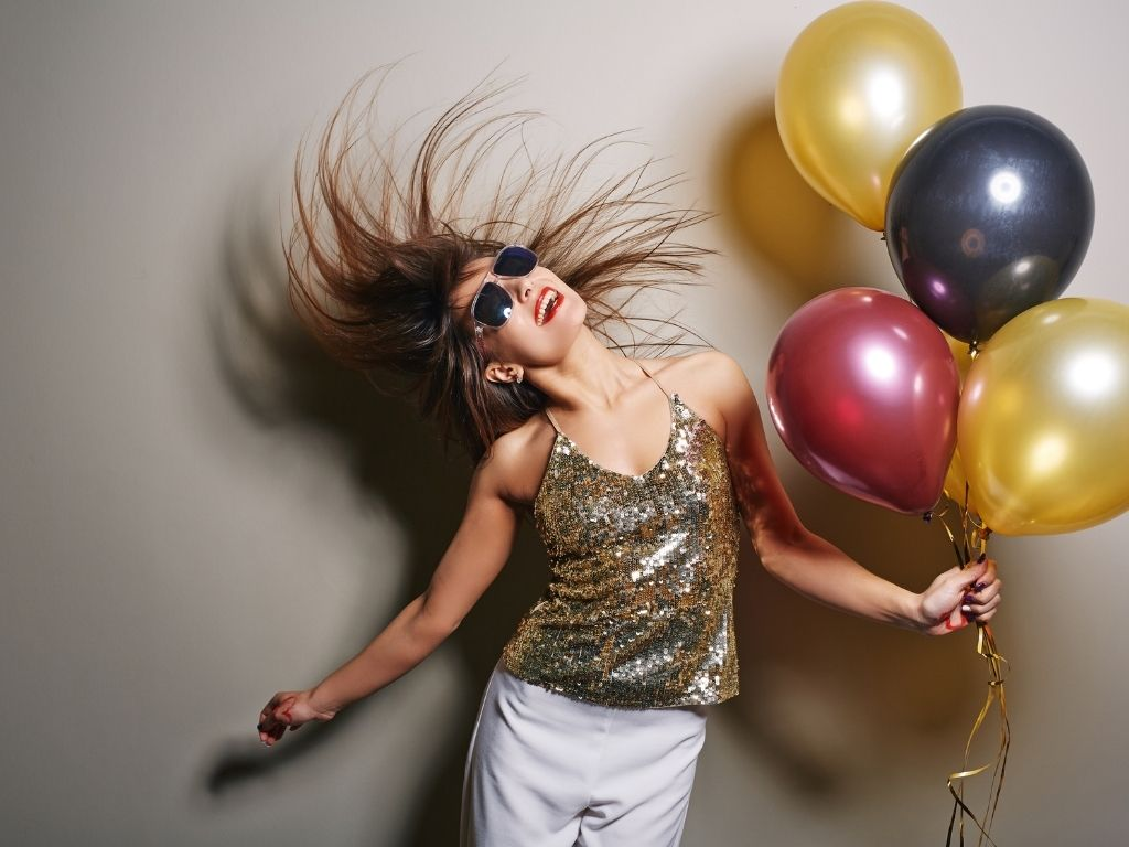 Woman in gold sequin top flipping her hair holding balloons