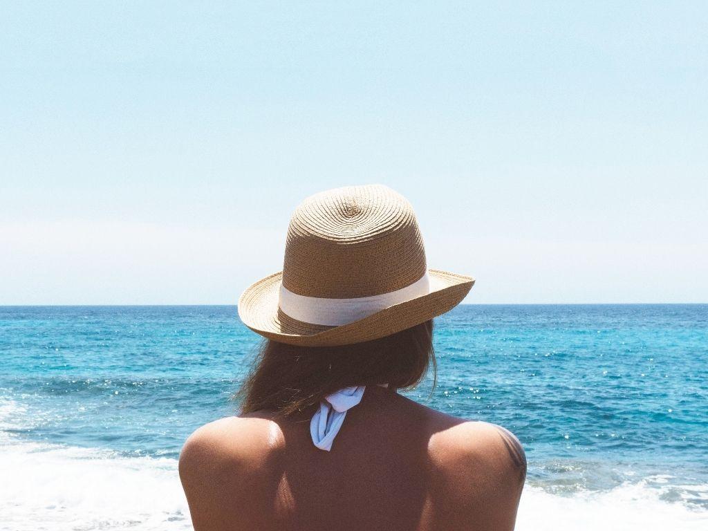 Woman in hat sitting on beach watching ocean