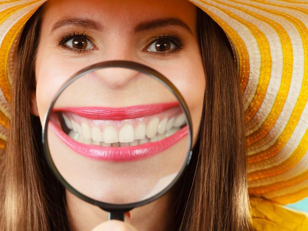 Closeup woman in summer hat smiling and showing teeth through magnifying glass