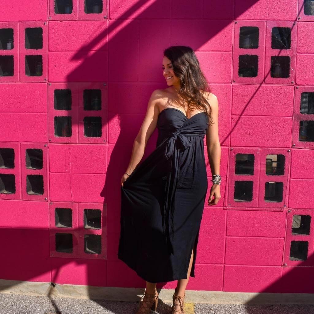 Brunette in black dress leaning on hot pink wall