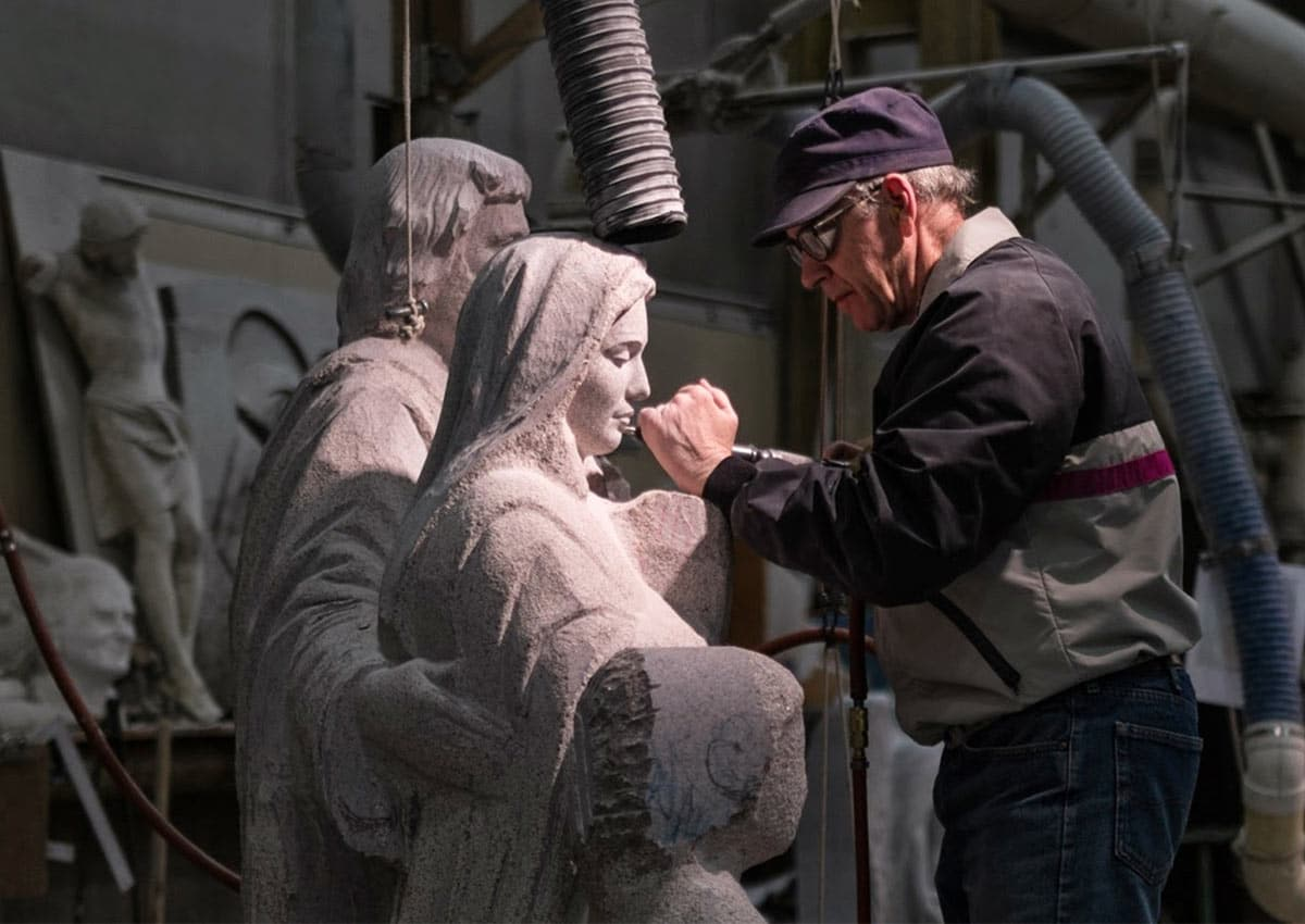 A sculptor finishes a detail in granite at Rock of Ages in Barre VT