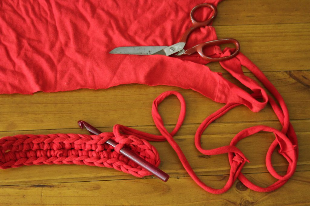 scissors laid looking like its cutting into fabric which unravels into yarn and a crochet hook lays looking likes its crocheting