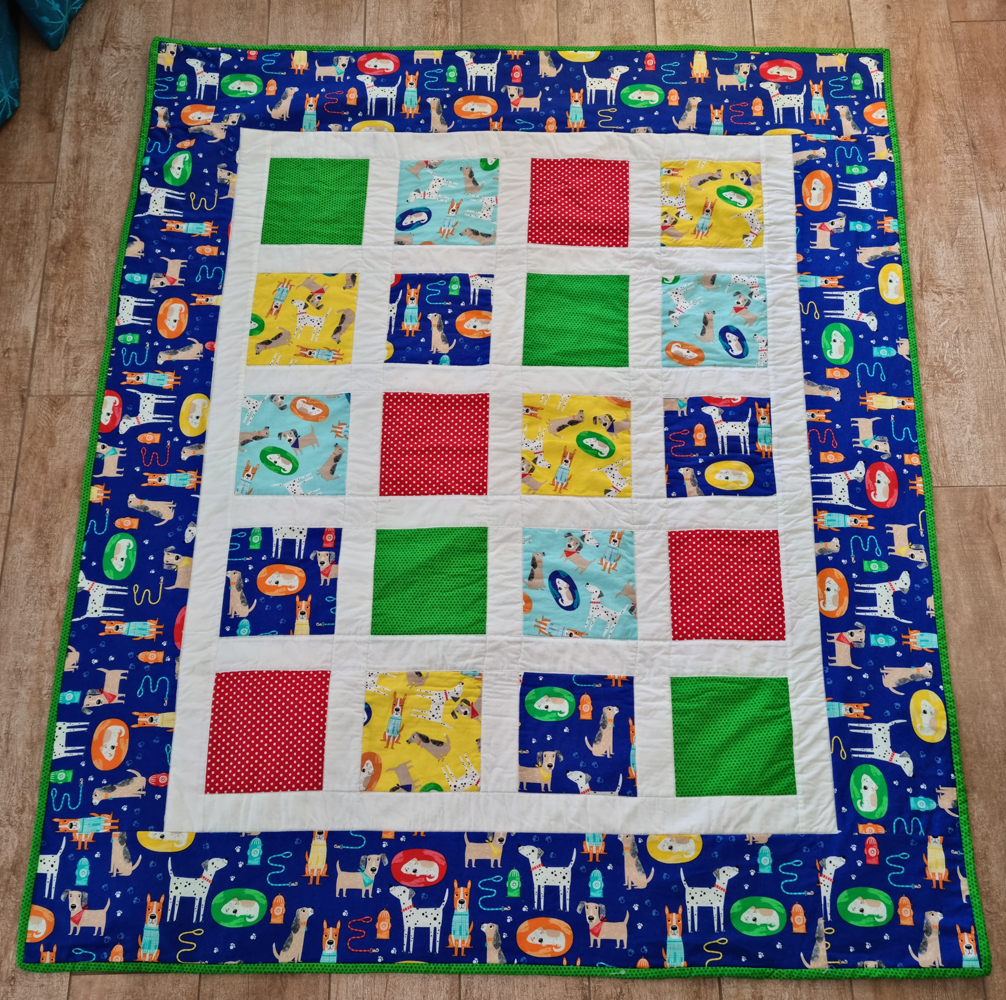 A baby quilt made with dog fabrics
