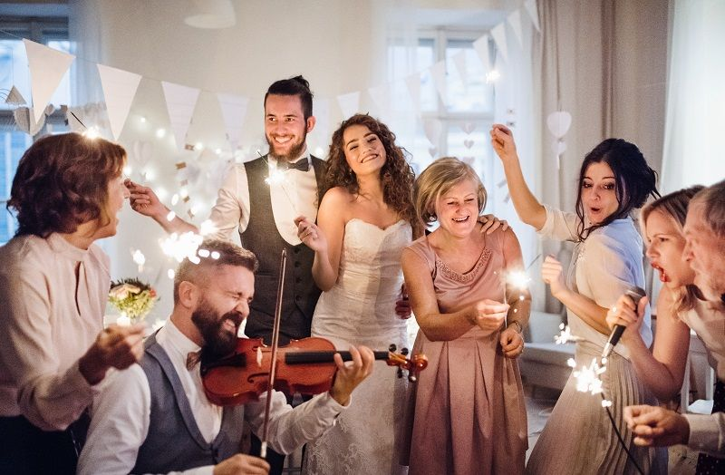 A young bride, groom and other guests dancing and singing on a wedding reception