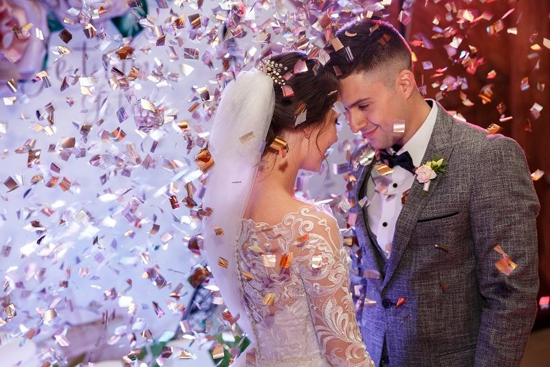Happy-bride-and-groom-dancing-under-confetti-at-wedding-reception.-cm