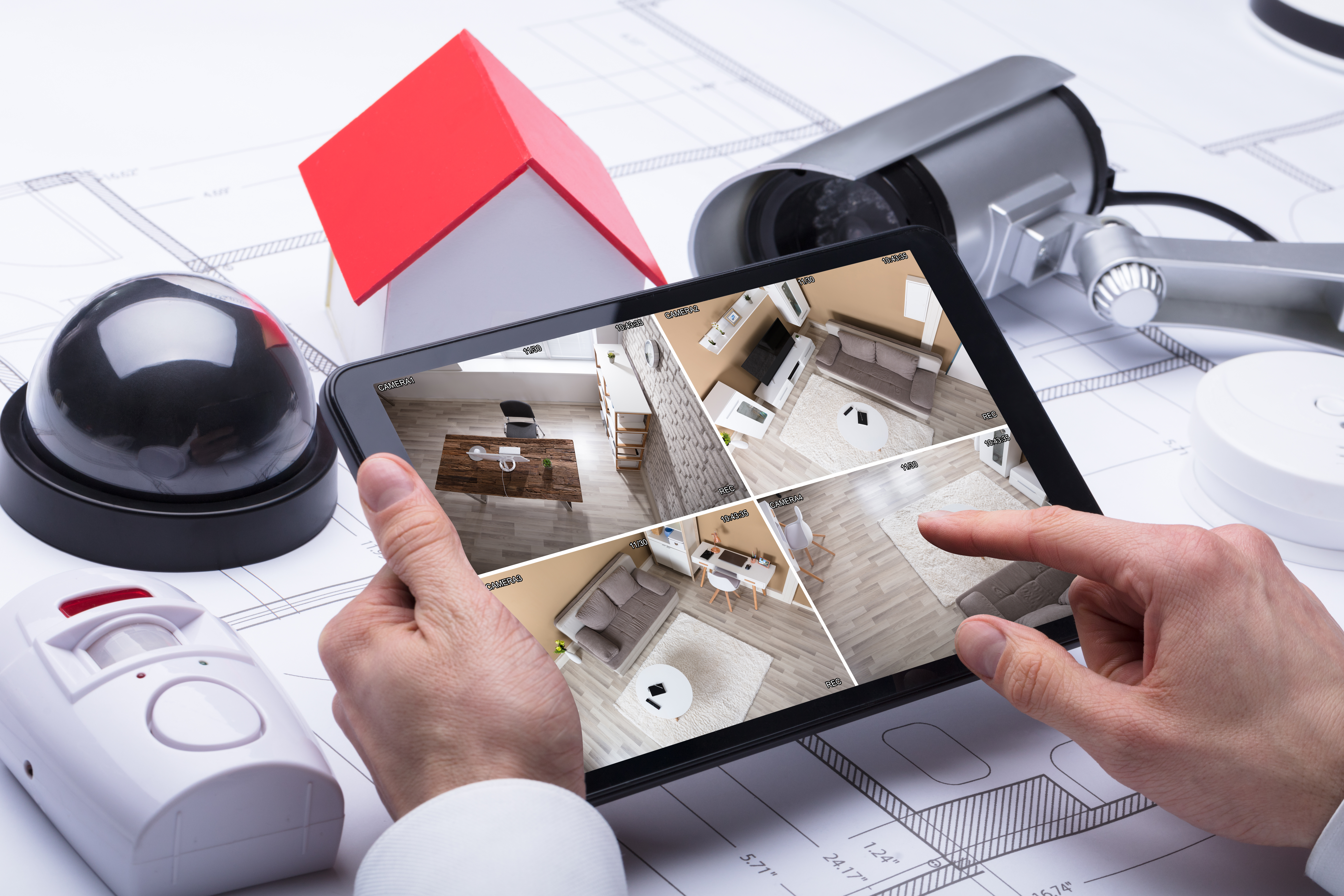 A Person Watching Footage On Digital Tablet With Security Equipments And House Model On Blueprint