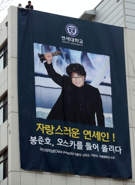 Yonsei University hangs a banner of Bong Joon Ho holding an Oscar Trophy.