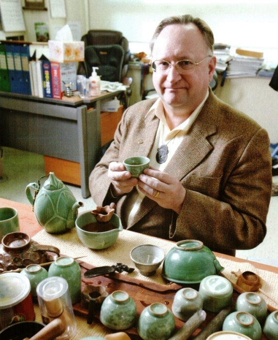 Professor David A. Mason drinking tea in his office.