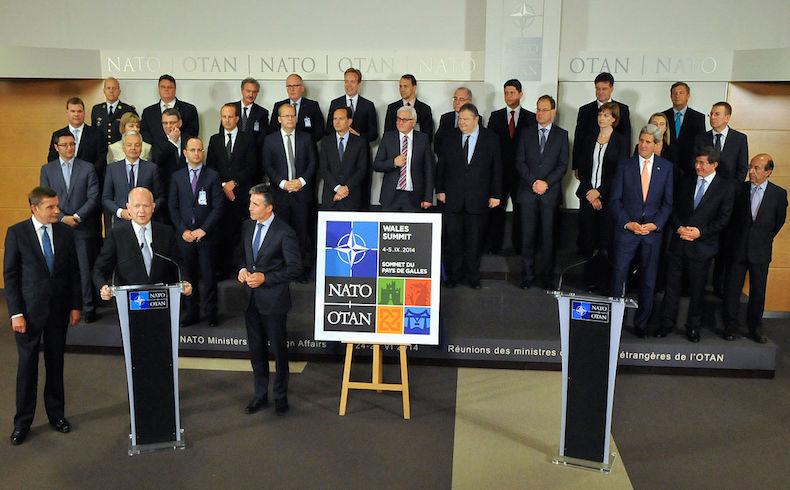 Secretario de Relaciones Exteriores británico, William Hague, saluda el logotipo de la Cumbre de la OTAN de 2014 en Gales, en septiembre de 2014.