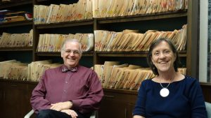 The folders behind them highlight how important paperwork skills are for volunteers of Dr. Leonard Reeves (left) and Barbara Earle at the Faith and Deeds Community Health free clinic.