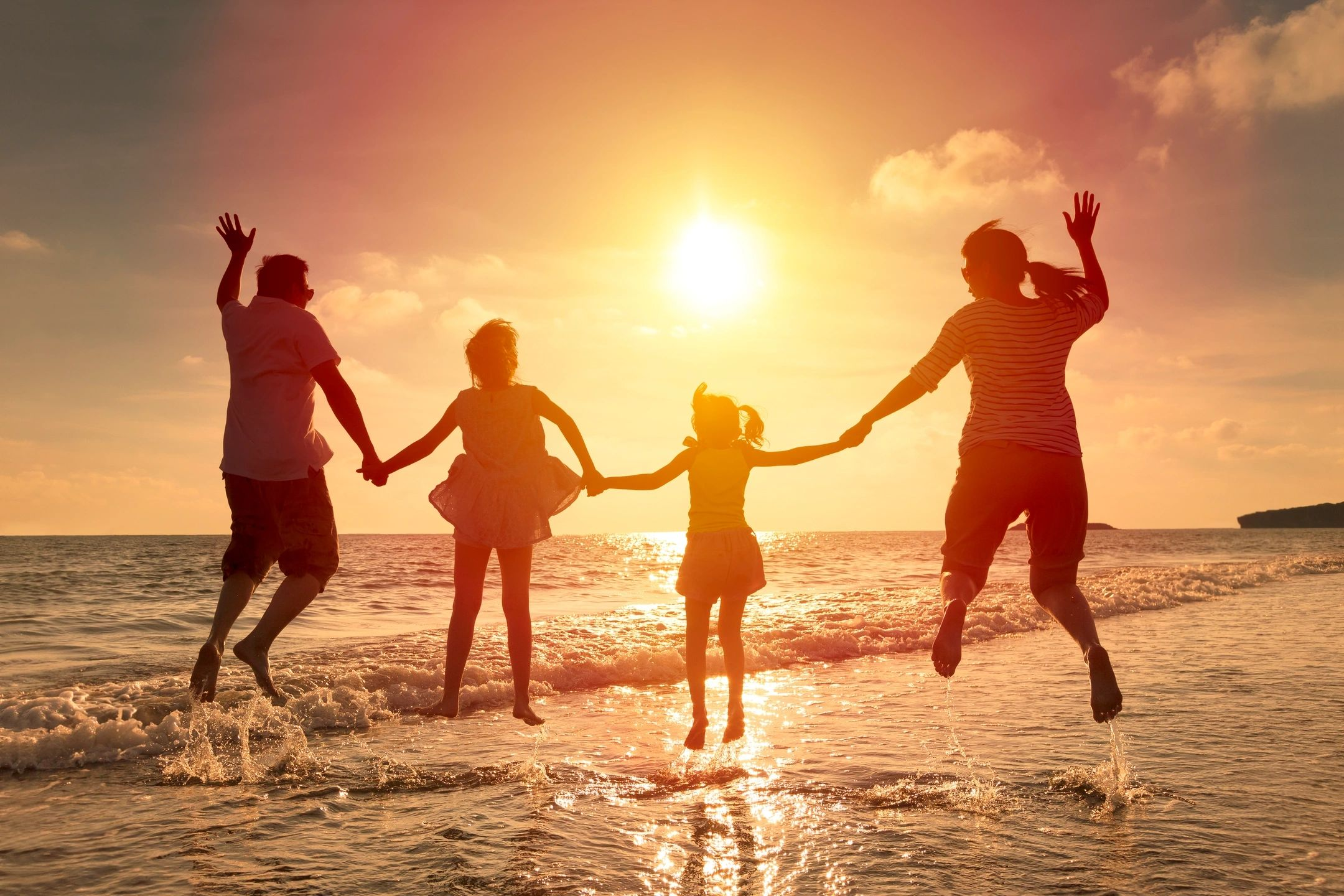 Happy family jumping at the beach