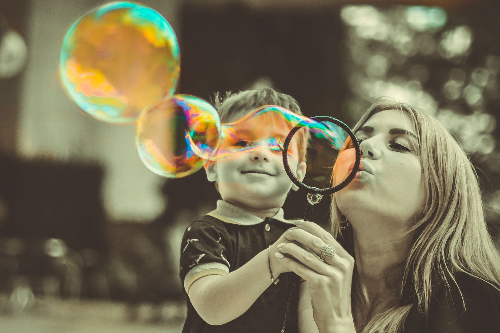 Boy with Autism blowing bubbles with a caretaker.