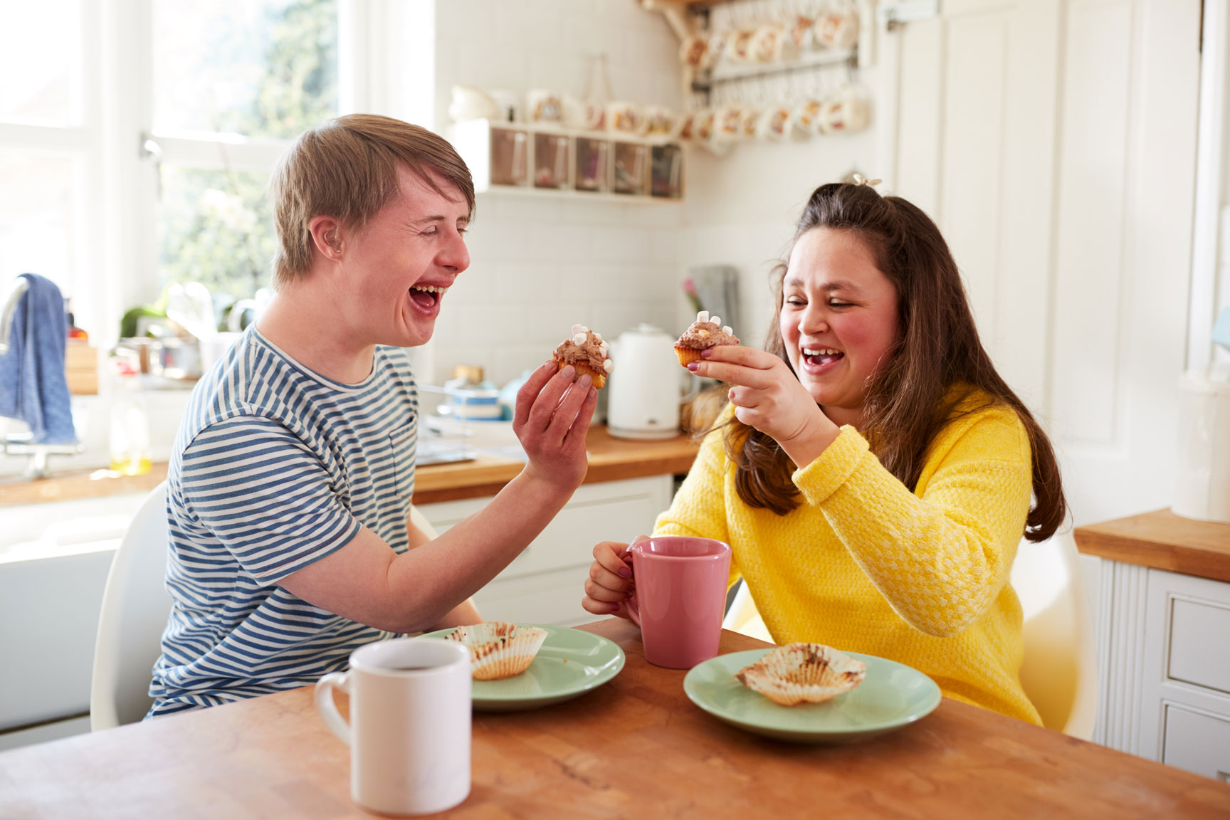 Boy with Down Syndrome eating muffins with a caretaker.