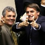 Os deputados Alberto Fraga e Jair Bolsonaro fazem sinal com as mãos imitando armas de fogo durante a votação em segundo turno do projeto