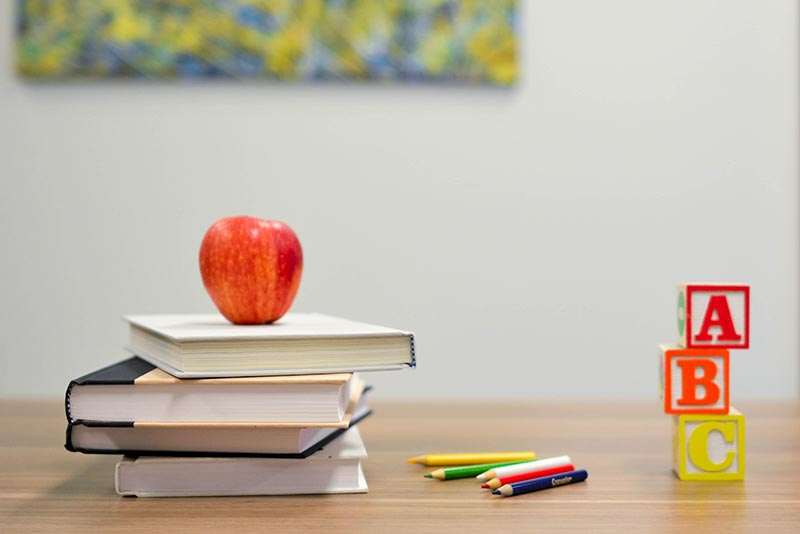 Image of apple on stacked books, coloring pencils and ABC blocks