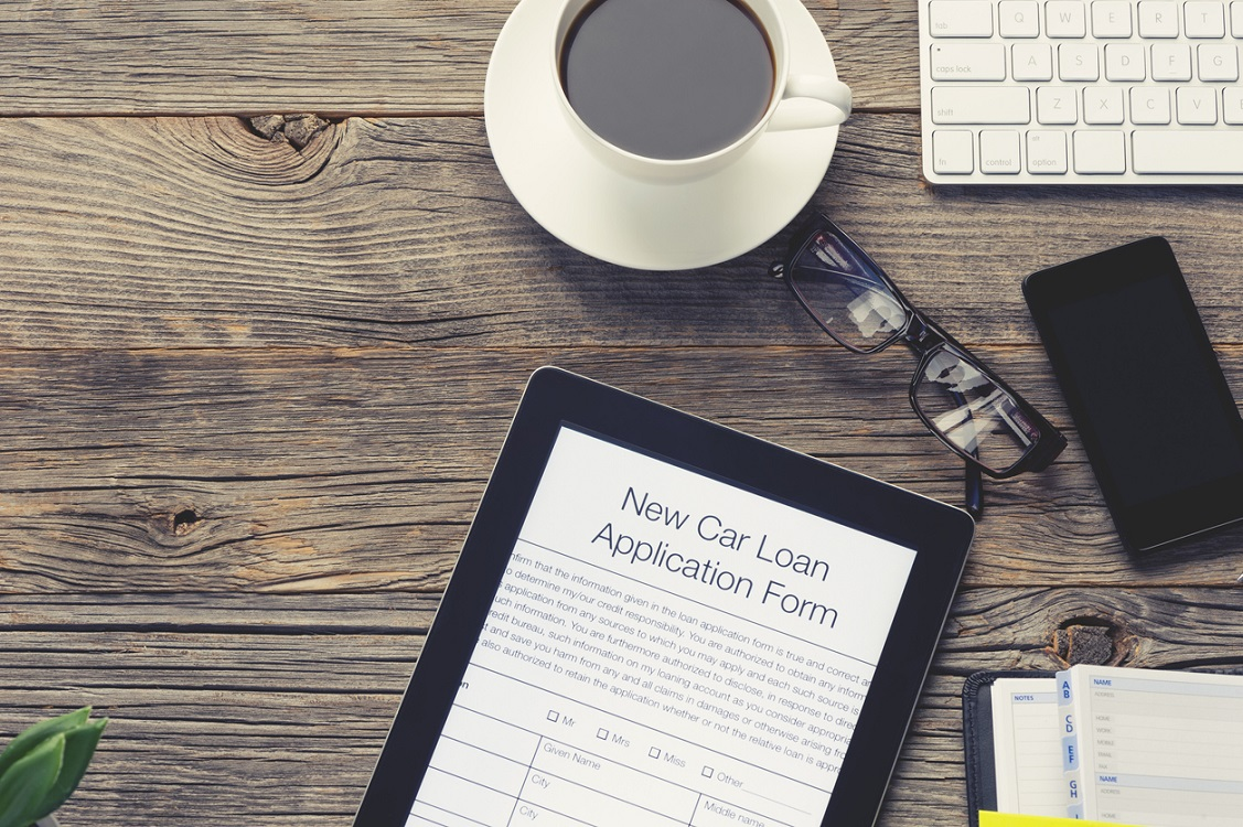 Online car loan application form. The document is displayed on a digital tablet. There is also a mobile phone, computer keyboard, coffee, Filofax organizer notepad and glasses on the table. The table is made of wood and is quite old. Copy space on left.