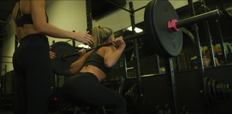 photo of woman squatting heavy weight with another woman behind spotting - exercise & fitness