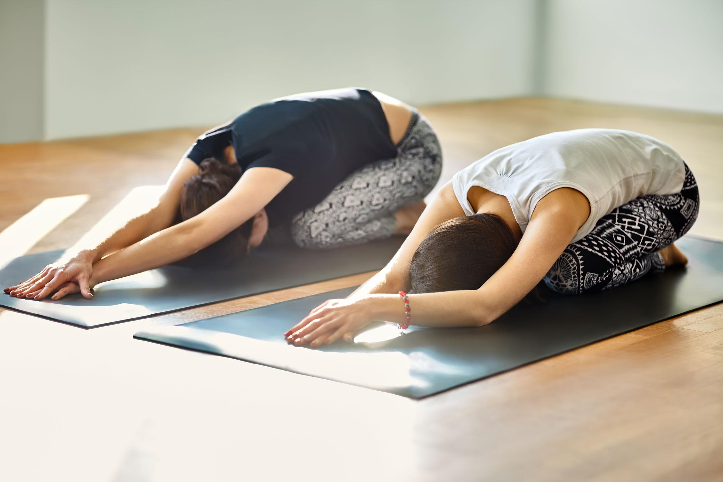 Two young women doing yoga asana child's pose