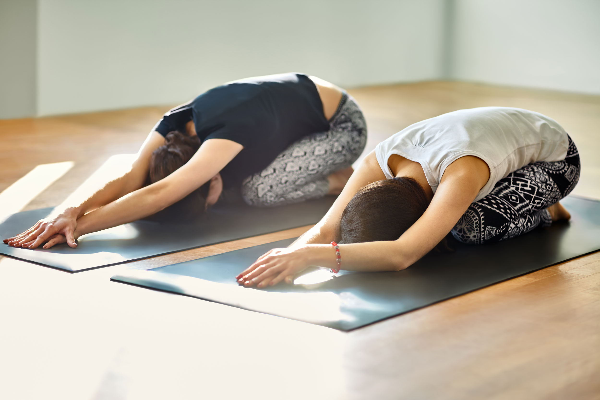 Two young women doing yoga asana child's pose
