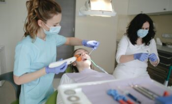 woman-in-light-blue-scrub-suit-holding-dental-curing-light-3952132
