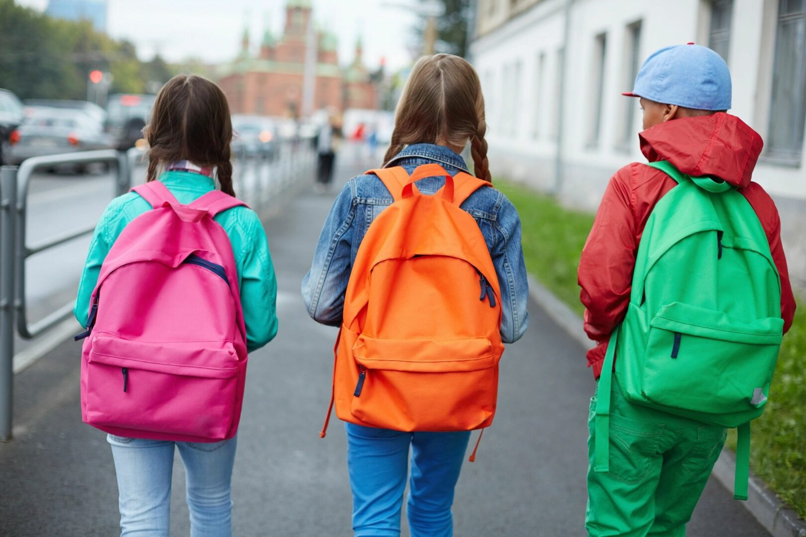 Back view three children wearing backpacks in different colors