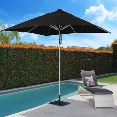 Reclining chair underneath an umbrella by a pool