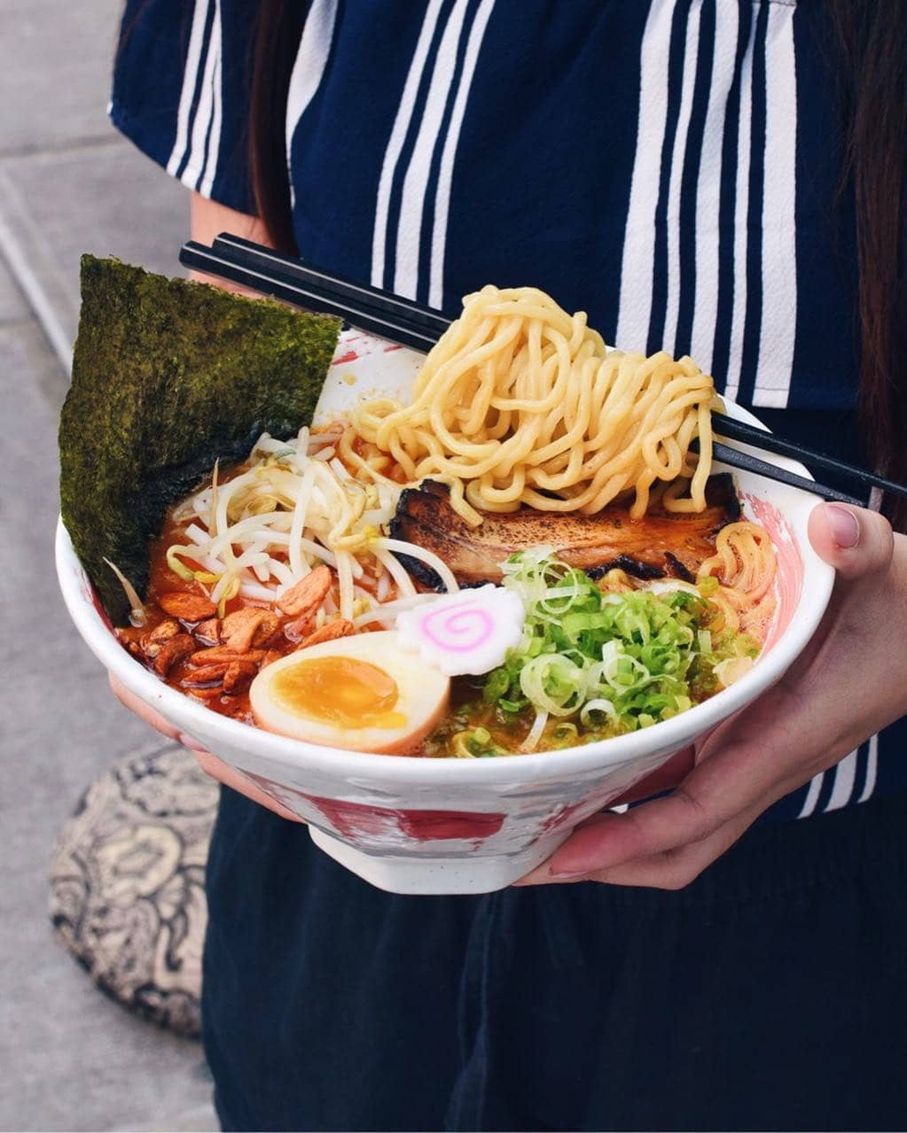 holding ramen bowl with noodles, eggs, bean sprouts