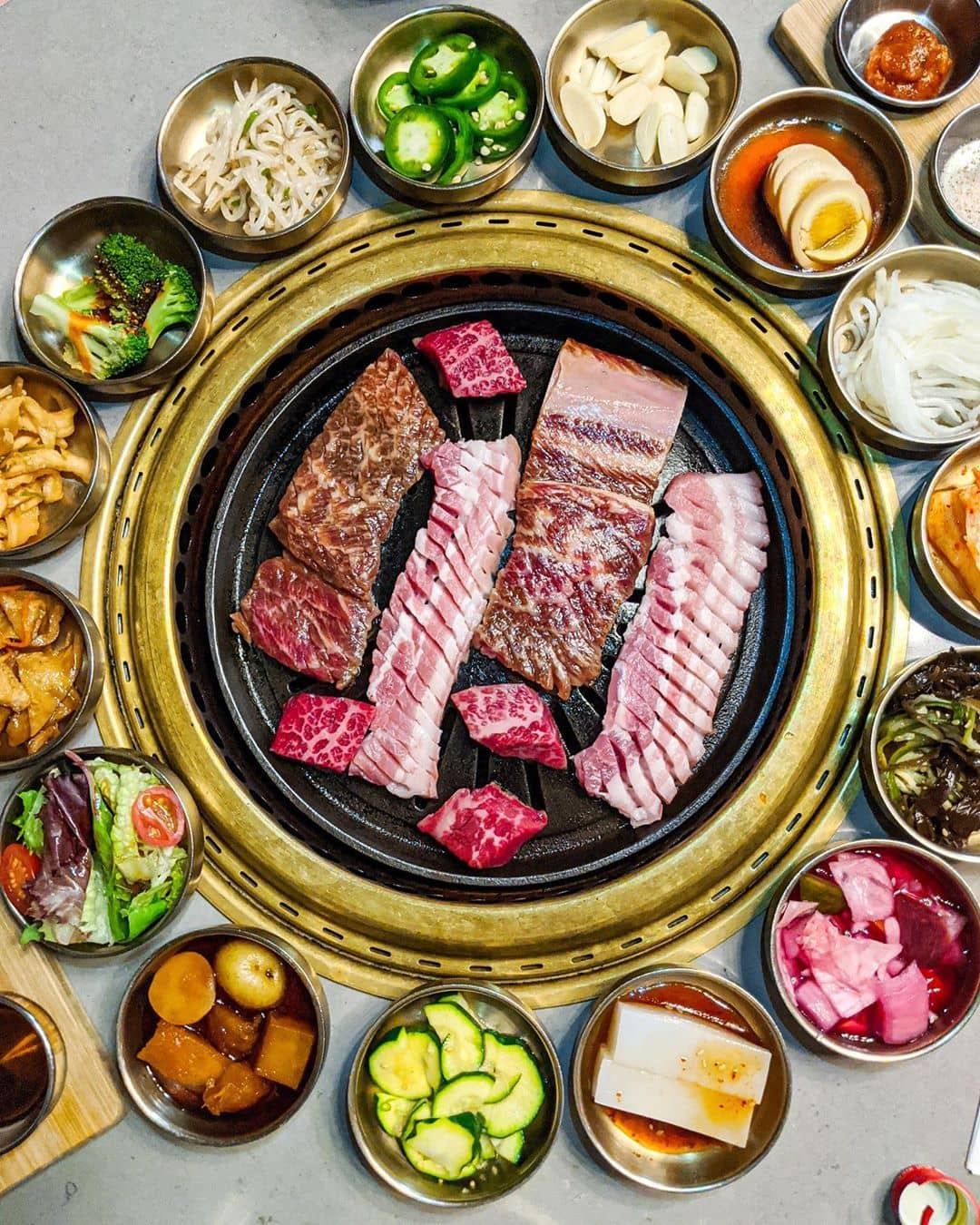 korean bbq meat on grill and small bowls banchan surrounding bbq